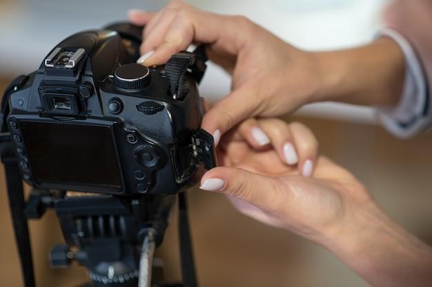 Gros plan des mains féminines mettant en place l'appareil photo tout en se préparant à tirer