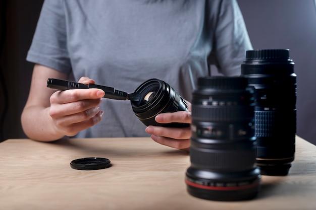 Gros plan des mains féminines nettoyant l'objectif de l'appareil photo numérique moderne avec un pinceau ou un pinceau professionnel, en éliminant la poussière.