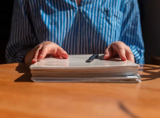 Gros plan des mains féminines avec une pile de documents sur une table en bois