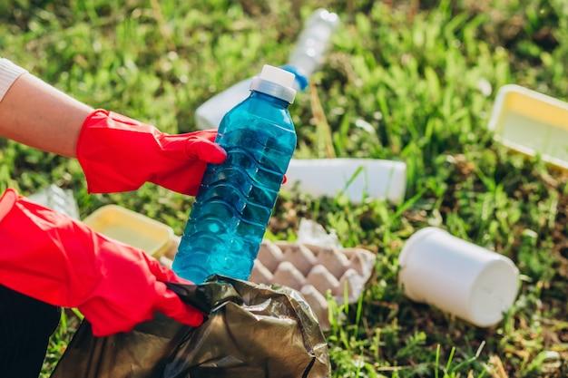 Gros plan des mains féminines portant des gants rouges et à l'aide d'un sac à ordures, ramasser des déchets en plastique pour le nettoyage au parc.