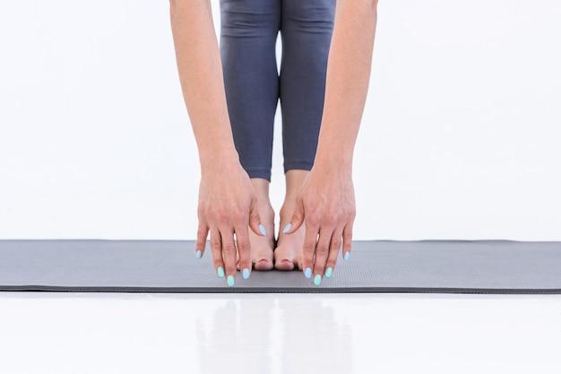 Gros plan des mains féminines qui s'étendent jusqu'aux jambes en se tenant debout sur le tapis dans le studio pratiquant le yoga