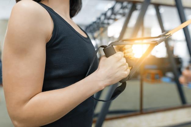 Gros plan des mains féminines avec des sangles de fitness dans la salle de gym