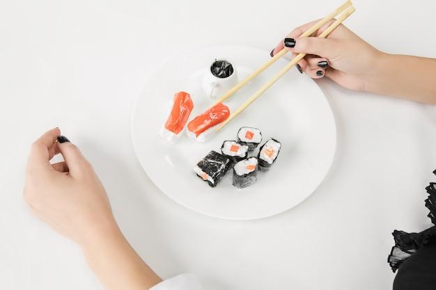 Gros plan des mains féminines avec des sushis en plastique, concept écologique. perdre le monde organique.