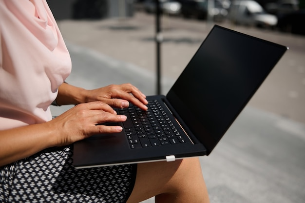 Gros plan sur des mains féminines tapant du texte sur un ordinateur portable avec un écran noir vierge avec un espace de copie pour la publicité sur le fond urbain. concept d'entreprise