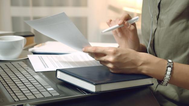 Gros plan des mains féminines tenant un contrat ou un rapport financier et prenant des notes sur le lieu de travail