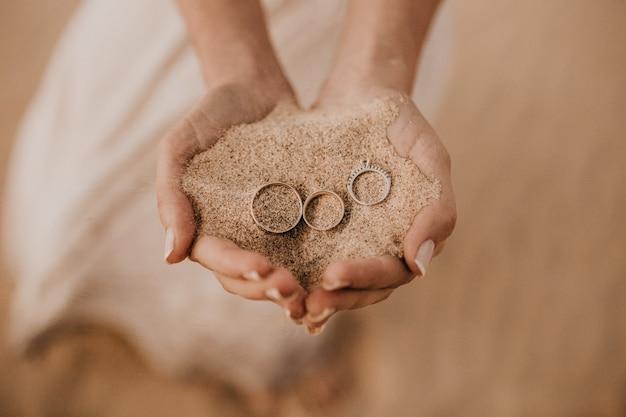 Gros plan des mains féminines tenant du sable avec trois anneaux sur le dessus