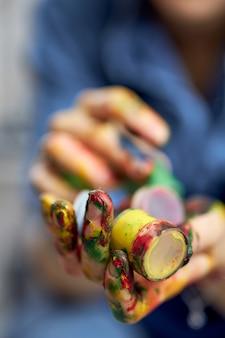 Gros plan de mains féminines tenant des peintures à l'huile acryliques colorées dans des pots