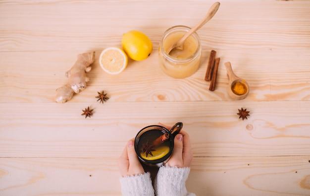 Gros plan des mains féminines tenant une tasse d'eau tiède au citron