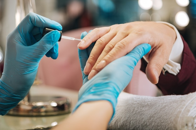 Gros plan des mains féminines vêtements gants bleus et application de vernis à ongles