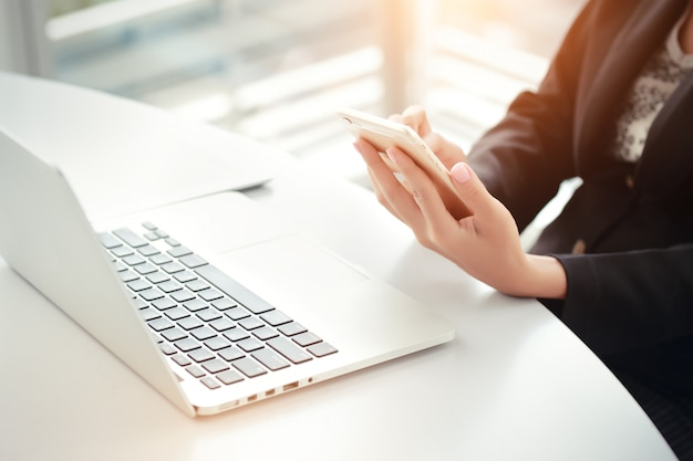 Gros plan des mains de femme d'affaires à l'aide d'un téléphone intelligent et écran tactile