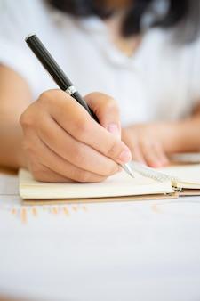 Gros plan des mains de femme d'affaires tenant un stylo écrit quelque chose