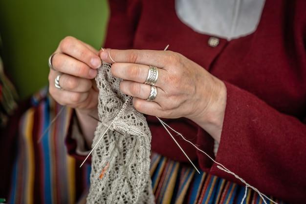 Gros plan des mains d'une femme âgée à tricoter.