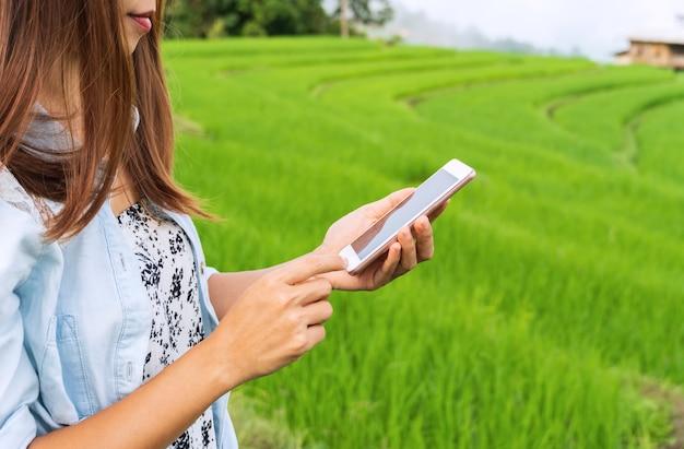 Gros plan des mains de femme à l'aide de smartphone à des terrasses de rizières