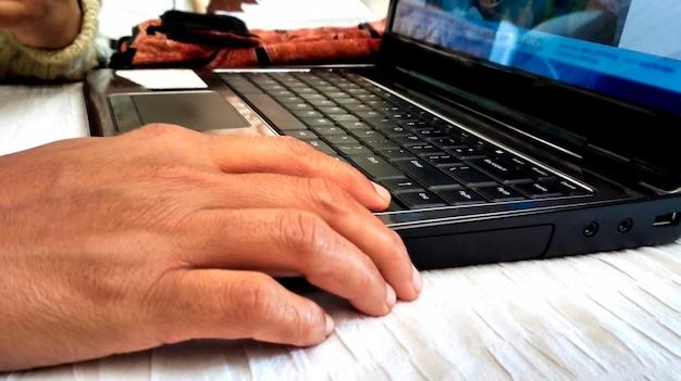 Gros plan sur les mains de la femme à l'aide de son ordinateur portable à la maison