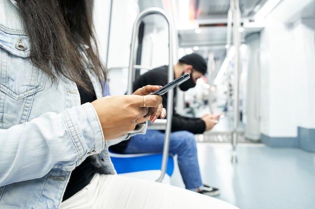 Gros plan des mains d'une femme et un en arrière-plan assis dans la voiture de métro à l'aide du smartphone