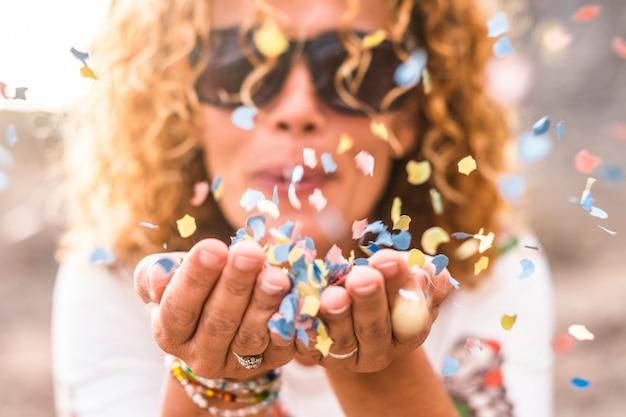 Gros plan sur les mains de la femme et la belle dame soufflant des confettis colorés du carnaval - concentrez-vous sur les papiers de couleurs et le bonheur et le concept de style de vie joyeux pour les gens heureux en plein air
