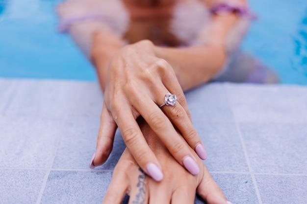 Gros plan des mains de la femme sur le bord de la piscine avec l'anneau au doigt