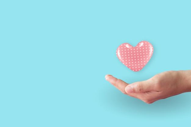 Gros plan des mains de femme avec coeur avec pastel propre.