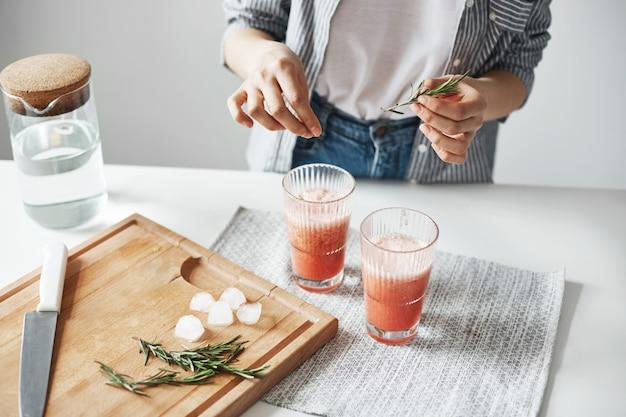 Gros plan des mains de femme décorer le smoothie sain de pamplemousse detox au romarin.