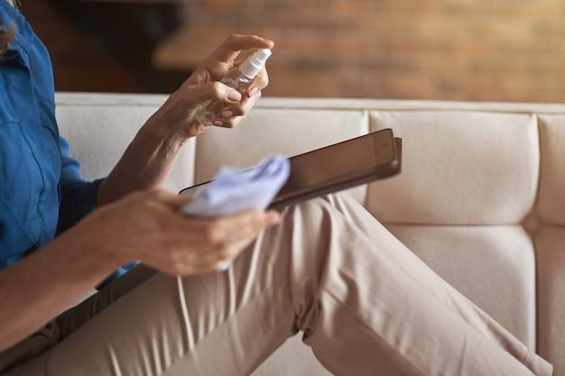 Gros plan sur les mains d'une femme désinfectant et nettoyant la tablette des virus microbiens et