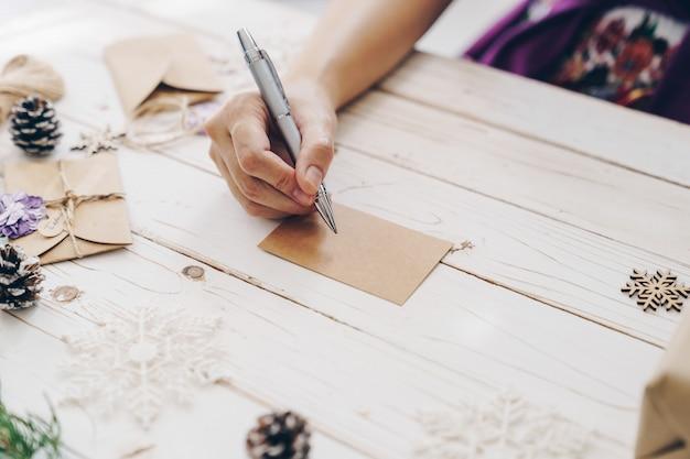 Gros plan des mains femme écrivant liste de souhaits vide et carte de noël sur table en bois avec décoration de noël.