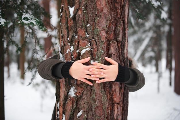 Gros plan des mains de la femme embrassant l'arbre
