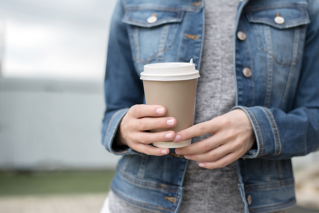 Gros plan sur les mains de la femme avec manucure rose dans une veste en jean