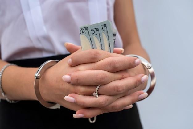 Gros plan des mains de femme menottes aux poignets tenant le dollar. pot-de-vin et corruption