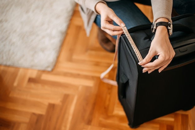 Gros plan des mains de femme mesurant les bagages avant de partir en voyage.