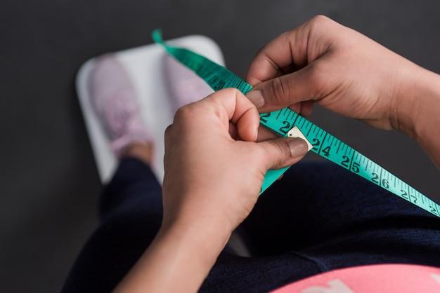 Gros plan des mains de femme portant des vêtements de sport mesurant la taille avec un ruban à mesurer.