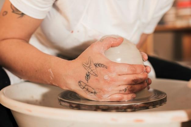 Gros plan des mains de femme potier avec de l'argile sur le tour de potier