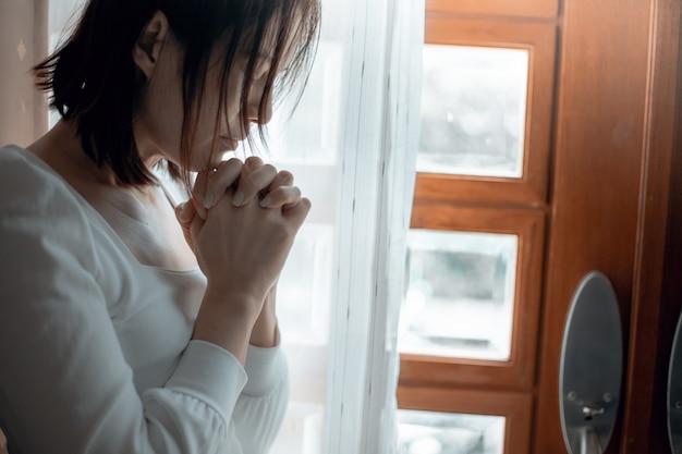 Gros plan des mains de femme priant à l'église, la femme croit et prie dieu.