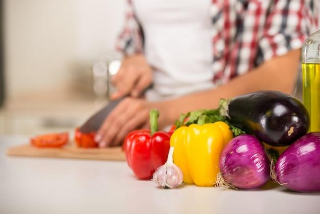 Gros plan des mains d'une femme qui coupe des légumes.
