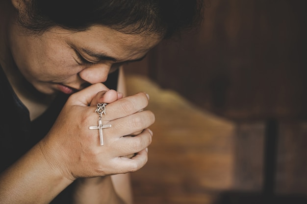 Gros plan des mains de femme senior chrétienne sur croix crucifiée en priant dieu.