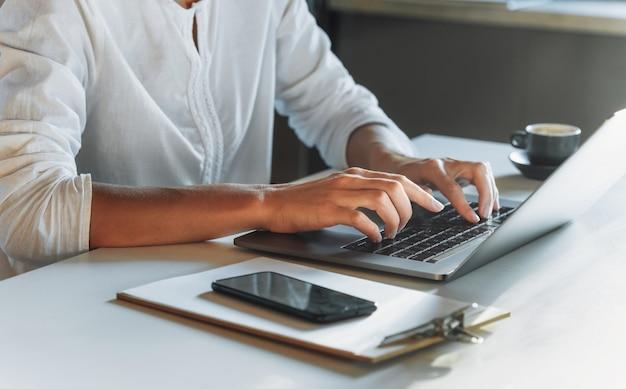Gros plan des mains de femme tapant sur le clavier à l'aide d'un ordinateur portable tout en travaillant ou en étudiant à domicile. éducation ou travail en ligne. concert de travail à distance