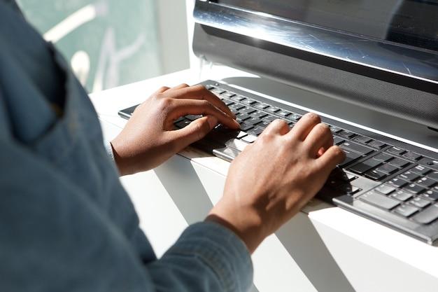 Gros plan des mains de femme en tapant sur un clavier d'ordinateur portable