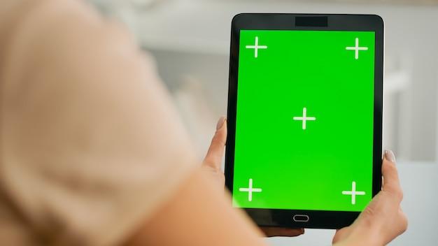 Gros plan sur des mains de femme tenant un ordinateur tablette avec un affichage de la clé chroma de l'écran vert mock up. indépendant assis sur un bureau dans le salon travaillant avec un appareil isolé pour un projet de style de vie en ligne