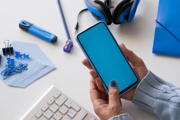 Gros plan sur les mains de la femme tenant un téléphone intelligent avec écran bleu. couleur bleue sur les accessoires
