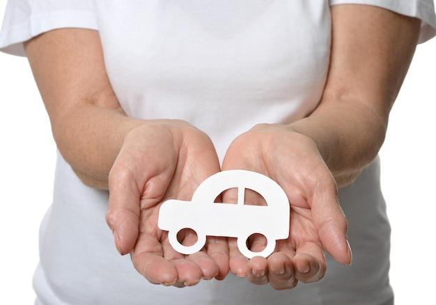 Gros plan des mains de la femme tenant une voiture modèle isolée sur fond blanc