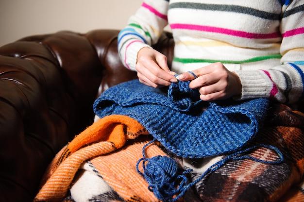 Gros plan des mains de femme à tricoter des fils de laine colorés.