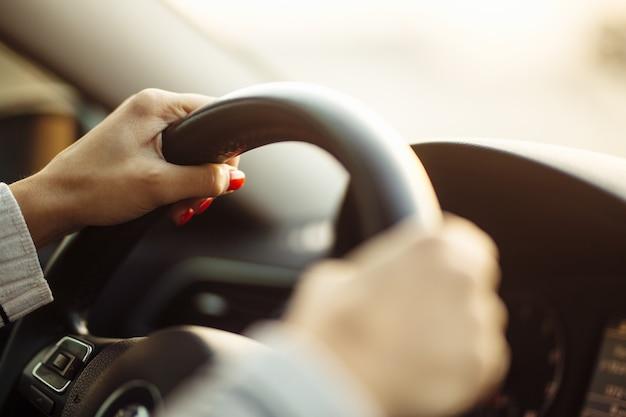 Gros plan des mains de la femme sur un volant en toute sécurité