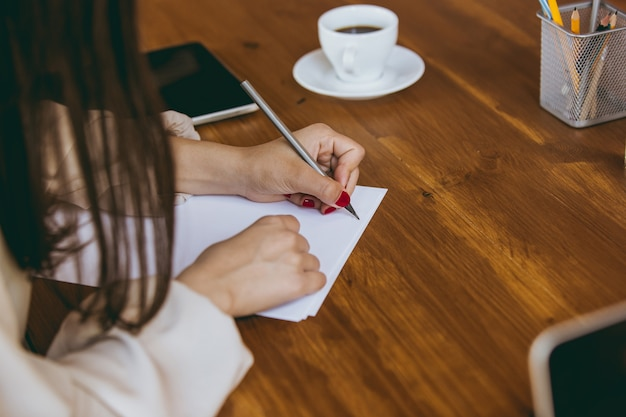 Gros plan sur les mains des femmes écrivant des notes lors d'une réunion créative, d'une discussion, d'un projet de travail au bureau. concept de finance, d'affaires, de pouvoir des filles, d'inclusion, de diversité, de féminisme. il a l'air heureux et attentif.
