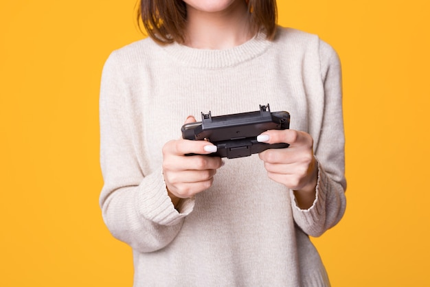 Gros plan des mains femmes jouant à des jeux vidéo e femme tenant le joystick sur fond isolé jaune