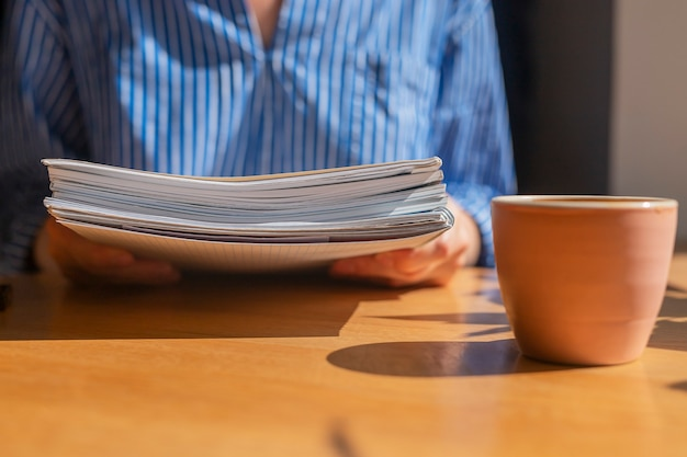 Gros plan des mains de femmes avec une pile de documents sur une table en bois au café