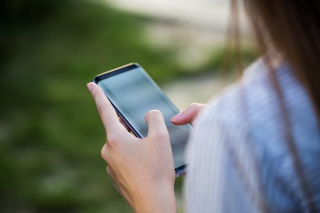Gros plan des mains de femmes tenant un téléphone cellulaire avec écran vide pour sms ou contenu promotionnel