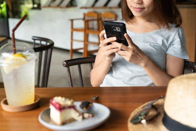 Gros plan des mains de femmes tenant un téléphone mobile au café.