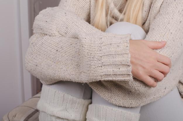Gros plan des mains de la fille dans un pull en laine décontracté étreignant ses genoux contre sa poitrine, se sentant seul