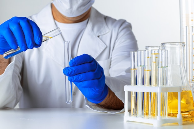 Gros plan des mains gantées d'un scientifique travaillant avec des échantillons de laboratoire