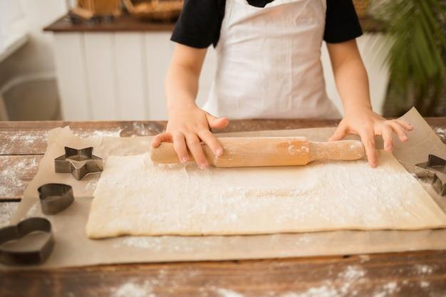 Gros plan des mains d'un garçon cuisinier étalant la pâte sur une table en bois avec un rouleau à pâtisserie