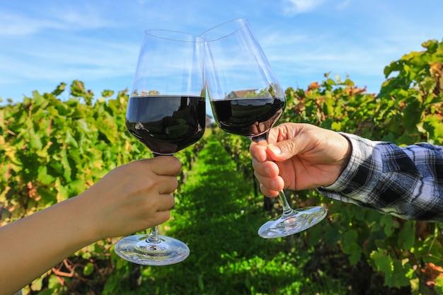 Gros plan sur les mains grillant des verres à vin rouge au vignoble